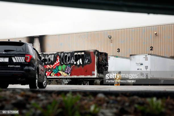 A firefighter inspects a refrigerated truck trailer that caught fire Thursday at Hannaford Distribution Center damaging the loading dock where it was...