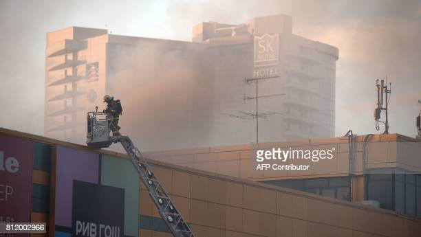 A firefighter inspects a rooftop as smoke rises from the Rio shopping mall in Moscow on July 10 2017 Ten people poisoned by smoke were hospitalised...