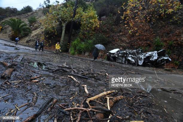 A firefighter instructs journalists to retreat to safer ground after a raindriven mudslide destroyed two cars and damaged property in a neighborhood...