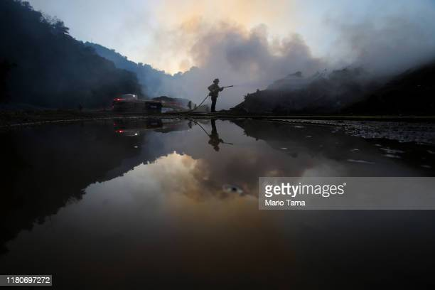 A firefighter is reflected in water while working during a flare up at a mulch supplier during the Saddleridge Fire on October 12 2019 in Sylmar...