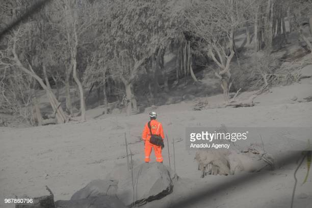 A firefighter is seen while he is searching along with other firefighters for their missing colleague in the area affected by the volcanic eruption...