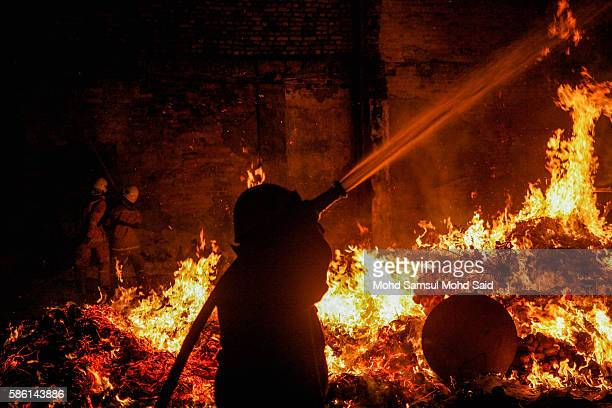 A firefighter is seen work near an effigy burn at the Hungry Ghost festival on August 6 2016 in Kuala Lumpur Malaysia The Hungry Ghost Festival falls...