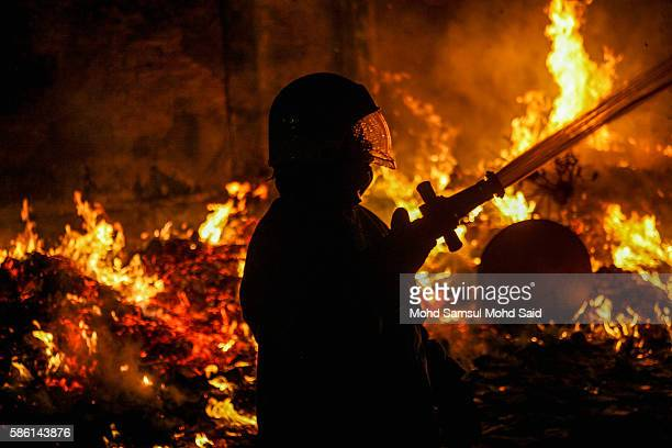 A firefighter is seen work near an effigy burn during Hungry Ghost Festival on August 6 2016 in Kuala Lumpur Malaysia The Hungry Ghost Festival falls...