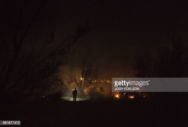TOPSHOT A firefighter is silhouetted as he walks along a hillside searching for spot fires in Lytle Creek California in the early morning on August...