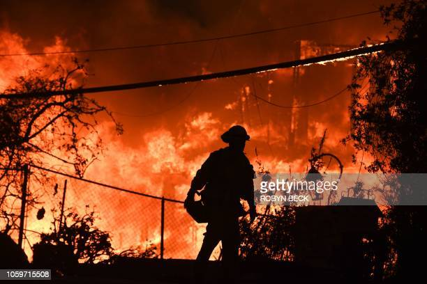TOPSHOT A firefighter is silhouetted by a burning home along Pacific Coast Highway during the Woolsey Fire on November 9 2018 in Malibu California...
