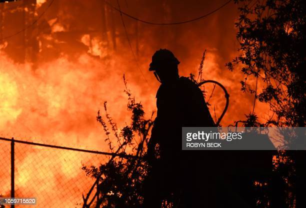 A firefighter is silhouetted by a burning home along Pacific Coast Highway during the Woolsey Fire on November 9 2018 in Malibu California About...