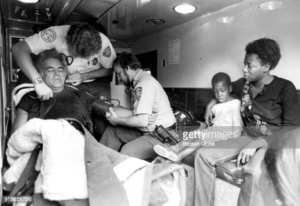Firefighter Jack Brignoli left is treated for smoke inhalation after the rescue of 4yearold Michael Riley who sits with his mother Loretta at right...