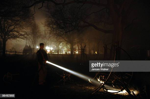 Firefighter James Johnson shines his flashlight on a burnt bench outside a home on December 27 2005 in Arlington Texas A grass fire in Arlington was...