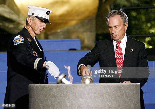 Firefighter John Vigiano and New York Mayor Michael Bloomberg light the Eternal Flame at the Sphere in Battery Park 11 September 2002 Vigiano lost...