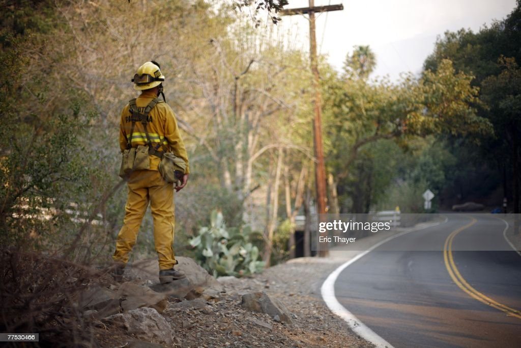 A firefighter keeps an eye on the Santiago fire October 26, 2007 in Silverado Canyon, California. With improving weather conditions firefighters continued to make progress against the wildfires in California. The fires caused the largest mass evacuation in California's history, burning nearly 500,000 acres, leaving a heavy toll on the county's agricultural industry and impacting an estimated cost to the state of one billion dollars.