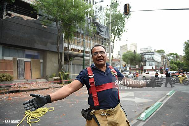 A firefighter keeps people at bay as a wall damaged during a quake is being demolished in Mexico City on May 8 2014 A strong 64magnitude earthquake...