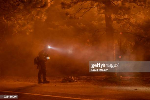 Firefighter keeps watch on flames that could jump the Angeles Crest Highway at the Bobcat Fire in the Angeles National Forest on September 11, 2020...