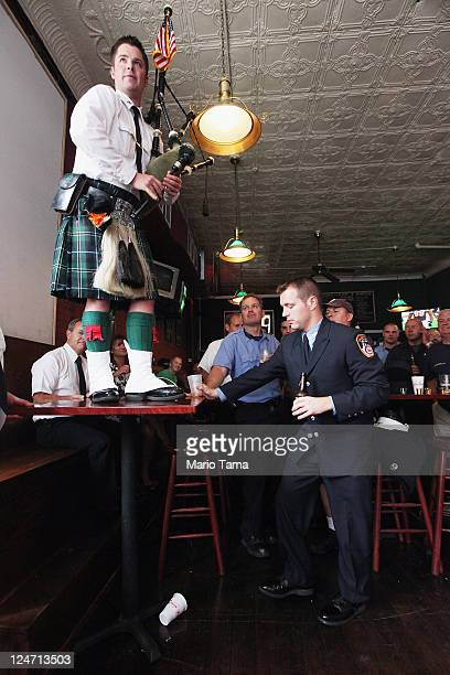 FDNY firefighter Kevin O'Connor plays bagpipes as firefighters look on at O'Connells Pub after a memorial service for firefighters killed on the 10th...