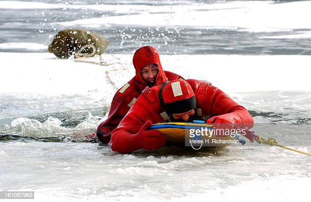 FIrefighter Laura Wright <cq> lays on the back of victim Kenny Shrum <cq> after having secured him to a rope while landbased firefighters help to...