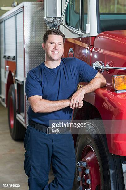 Firefighter leaning against fire rescue truck at station