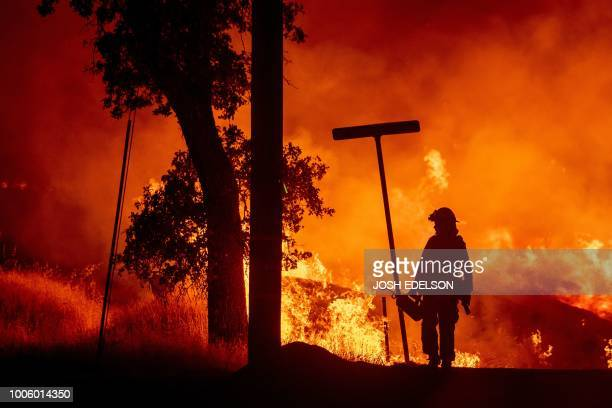 A firefighter lights backfires during the Carr fire in Redding California on July 27 2018 One firefighter has died and at least two others have been...