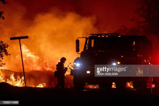 TOPSHOT A firefighter lights backfires during the Carr fire in Redding California on July 27 2018 One person has died and at least two others have...