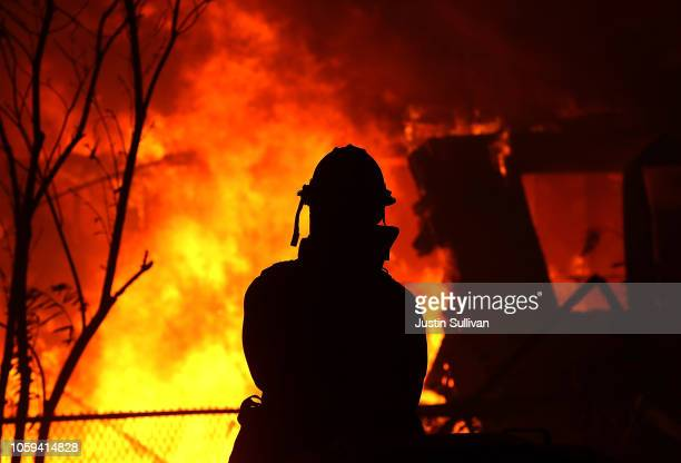 A firefighter looks on as a home is consumed by the Camp Fire on November 8 2018 in Paradise California Fueled by high winds and low humidity the...
