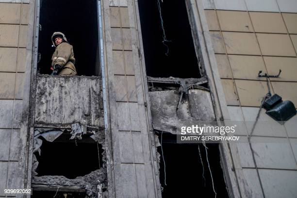 A firefighter looks out from inside the firegutted shopping mall in the industrial city of Kemerovo in western Siberia on March 29 2018 / AFP PHOTO /...