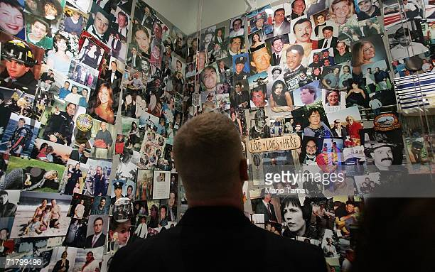 A firefighter looks photos of victims at the opening of the new Tribute Center September 6 2006 in New York City The Tribute Center is located across...