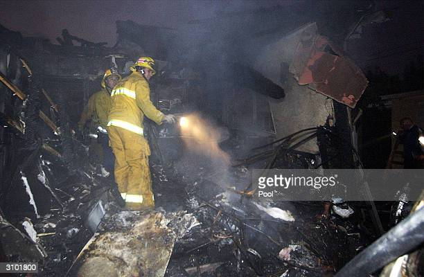 A firefighter looks through the wreckage of a small plane that crashed into a house March 16 2004 in Santa Monica California Reports say that the...