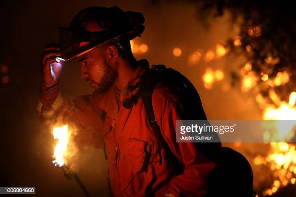 A firefighter monitors a backfire while battling the larger Carr Fire on July 27 2018 in Redding California A firefighter was killed battling the...
