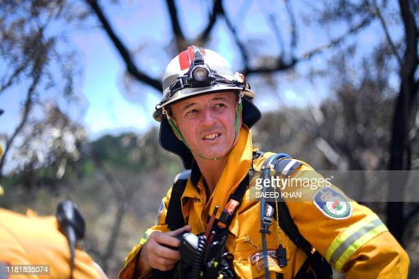 A firefighter monitors bush fires at the Woodford residential area in Blue Mountains on November 12 2019 A state of emergency was declared on...