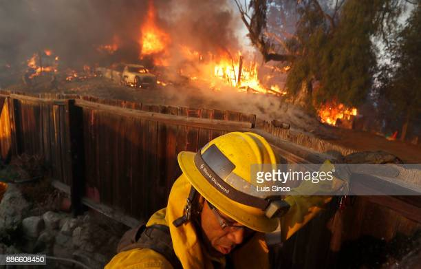 A firefighter monitors the Creek Fire as it burns a house inear the intersection of Johanna Avenue and McBroom Street in Shadow Hills on Tuesday Dec...