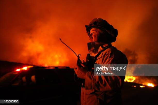A firefighter monitors the Kincaide Fire as it burns through the area on October 24 2019 in Geyserville California Fueled by high winds the Kincaide...