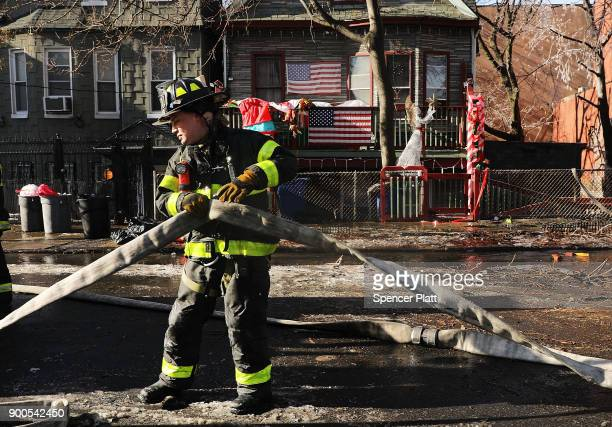 A firefighter moves hose after fighting a 7alarm fire in the Bronx on January 2 2018 in New York City The fire which started around 530 am on a...