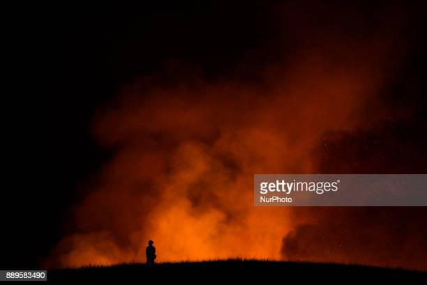 Firefighter Nick Tyler monitors the Thomas wildfire as it burns in the hills of Ojai, California on December 9, 2017. The wind-fueled fire burned...