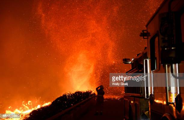 A firefighter observes a fire tornado from an overpass above the 101 freeway on December 6 2017 in Ventura California