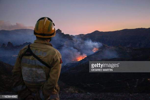 TOPSHOT A firefighter observes flames rising from a forest fire near the village of Ayacata in Tejeda on the island of Gran Canaria on August 20 2019...