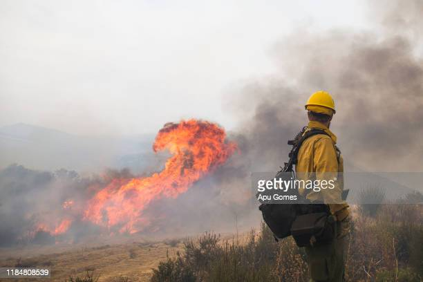 Firefighter observes the Cave fire burning at Los Padres National Forest on November 26 2019 in Santa Barbara California The fire has caused...