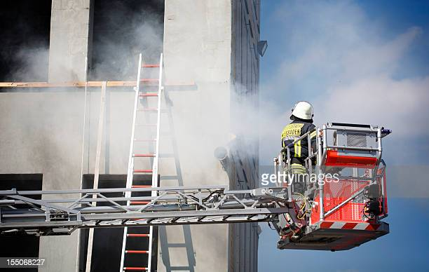 firefighter on a hydraulic platform - fire station stock photos and pictures