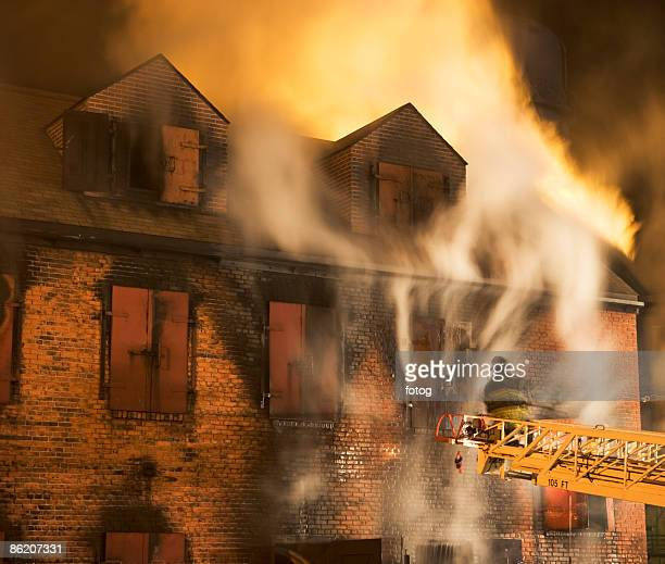 Firefighter on crane fighting building fire