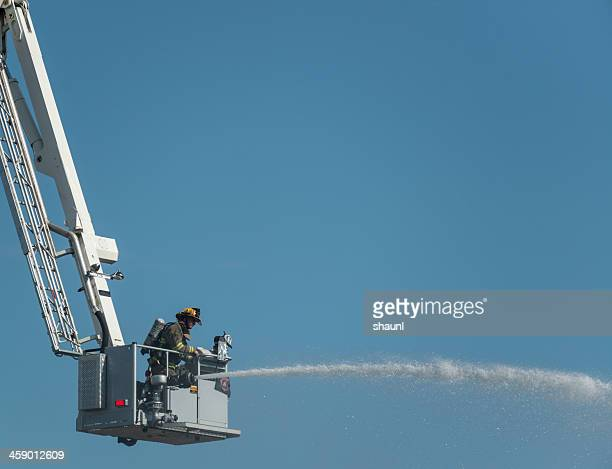 firefighter on ladder truck - firefighter's helmet stock photos and pictures