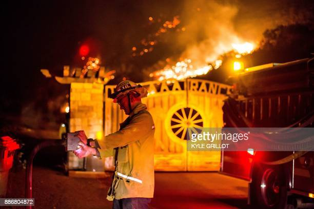 A firefighter opens a gate to investigate a house threatened by the Creek Fire burns along a hillside near homes in the Shadow Hills neighborhood of...