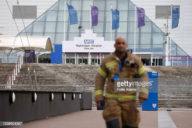 A firefighter outside the new NHS Nightingale Hospital at ExCeL London on March 29 2020 in London England The field hospital will initially contain...
