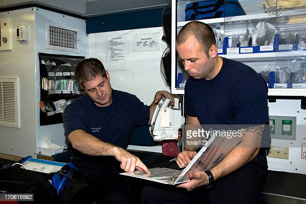firefighter paramedics checking equipment in ambulance. emergency, medical, technician. - fire station stock photos and pictures