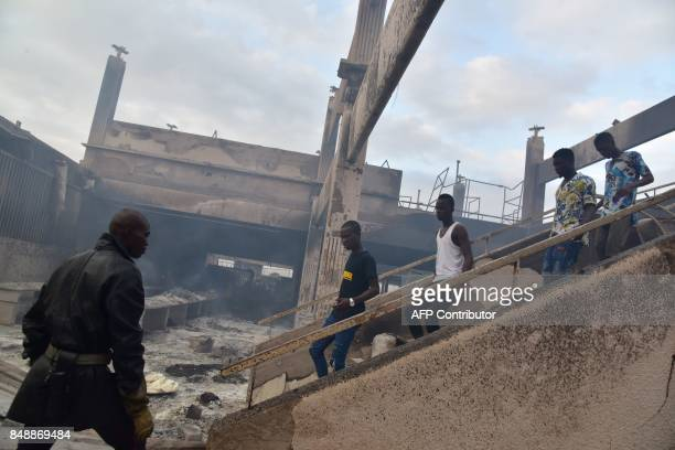 A firefighter passes by people walking down the stairs in the market after a fire devastated the building during the night on September 18 2017 in...