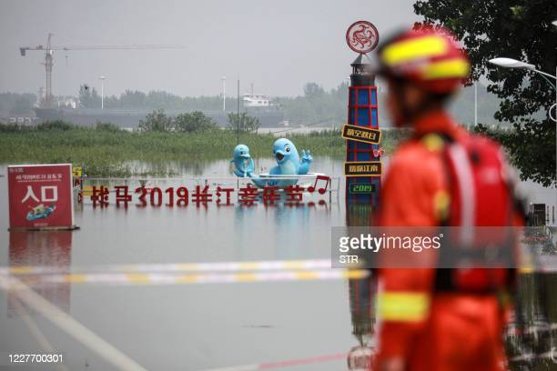 Firefighter patrols along a levee near the Yangtze river in Zhenjiang, in China's eastern Jiangsu province on July 20, 2020. - Rising waters across...