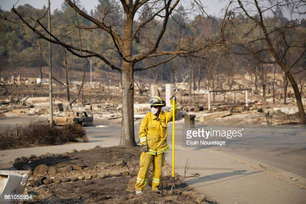 Firefighter pauses for a moment after looking through the rubble of a home in the Fountaingrove neighborhood on October 13, 2017 in Santa Rosa,...