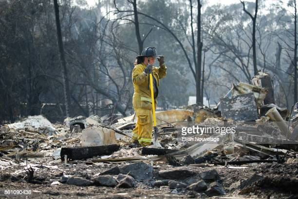 A firefighter pauses for a moment while looking through the rubble of a home in the Fountaingrove neighborhood on October 13 2017 in Santa Rosa...