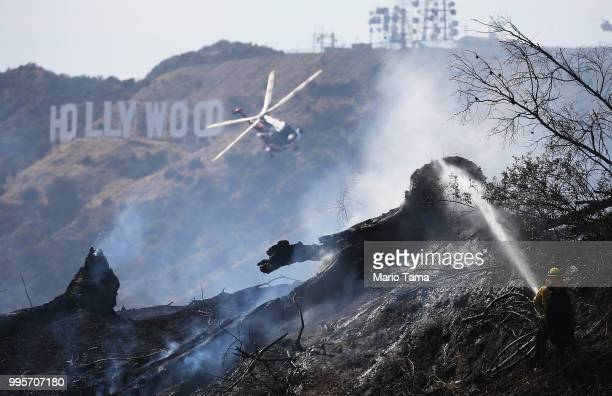 Firefighter personnel, including a helicopter crew, battle the Griffith fire at Griffith Park near the historic Griffith Observatory and the iconic...