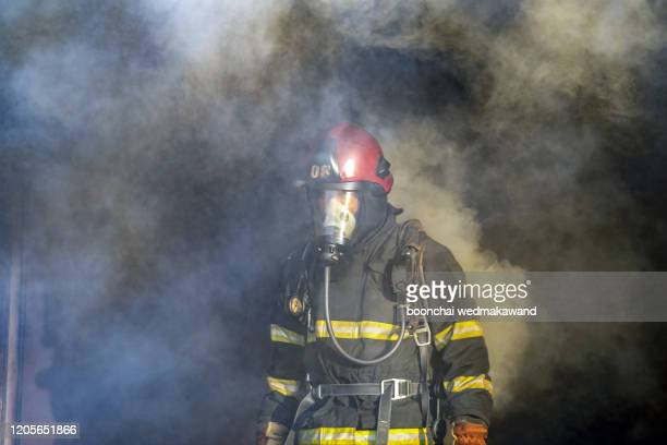 a firefighter pierces through a wall of smoke searching for survivors. - air attack stock pictures, royalty-free photos & images