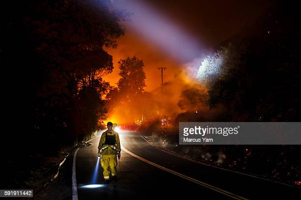 Firefighter point their beam lights around a burnt area to check for damages made by the Blue Cut fire that is burning north of the Lyle Creek...