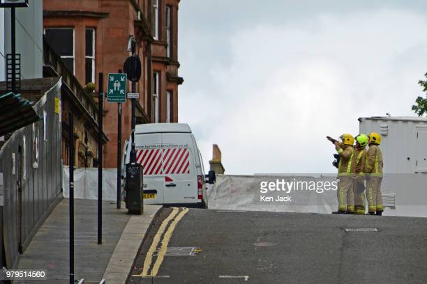A firefighter points towards the Glasgow School of Art Mackintosh building which was completely burned out in a major fire still carry recognisable...