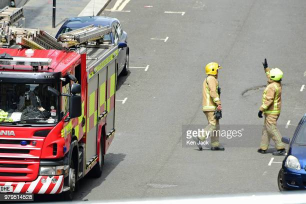 A firefighter points towards the roof of the Glasgow School of Art Mackintosh building which was completely burned out in a major fire still carry...
