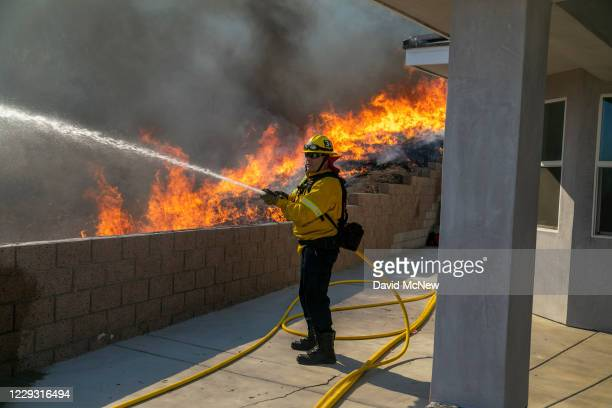Firefighter protects a home from getting too hot as a backfire is set to protect homes and try to contain the Blue Ridge Fire on October 27, 2020 in...